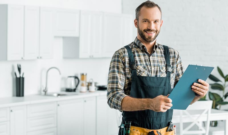 young professional holding a notepad standing inside of a kitchen